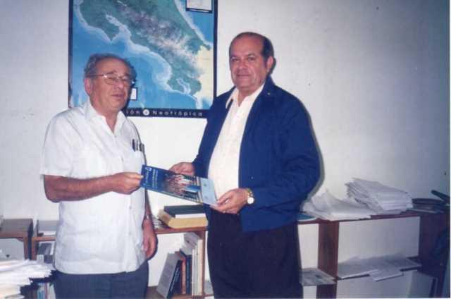 """En la sede la UNIVERSIDAD PARA LA PAZ  - Costa Rica - el Dr. Gerardo Budowsky – en su calidad de rector de la misma – recibe el informe de la maestría sobre """"Calidad Turística-Ambiental Sostenible y Promoción de la Paz"""", que se celebró en las Islas Canarias (1999-2012) con un programa elaborado por la citada universidad, de las Naciones Unidas, y el Instituto Superior de Estudios Turístico Internacionales, con sede en la Villa de la Orotava, isla de Tenerife. (Foto UPAZ)"""